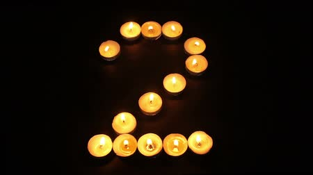 капелька : Static shot of burning tealight candles arranged like pixel art numeral digits to represent the number two on a black background.