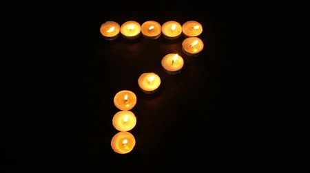 sete : Static shot of burning tealight candles arranged like pixel art numeral digits to represent the number seven on a black background. Stock Footage