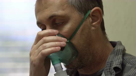 Close up side view shot of a suffering man wearing a medical nebulizer breathing mask that administers medicines to help alleviate persons with lung problems.