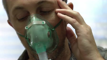 Close up frontal shot of a suffering man wearing a medical nebulizer breathing mask that administers medicines to help alleviate persons with lung problems. Stock Footage