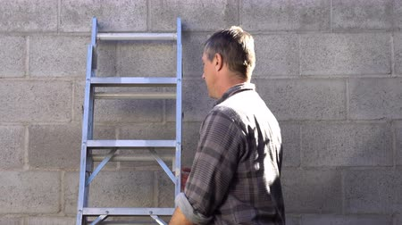Outdoor shot of a man walking into the shot and picking up a stepladder and then carrying it off to do some house work or home repairs. Stock Footage