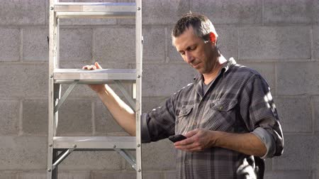 Man holding a ladder outside looks at his cellular mobile phone and he puts the ladder down and walks away into the camera.