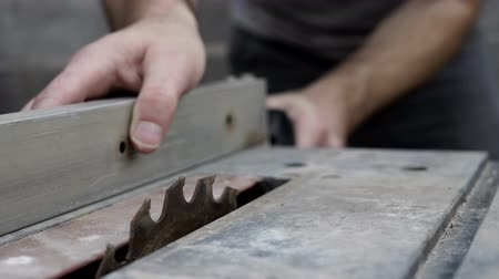 Close up shot of an anonymous man moving the fence or guide on a small table saw used to cut wood while cabinetmaking or woodworking.