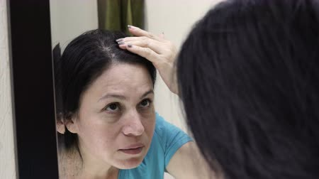 tuvalet : A handheld over the shoulder shot of a middle aged woman looking in a bathroom mirror and moving her hair around to check for gray hairs and signs of aging. Stok Video