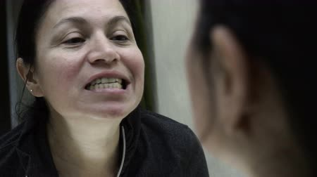 Close up over the shoulder shot of a woman looking into the bathroom mirror and inspecting her teeth. Stock Footage
