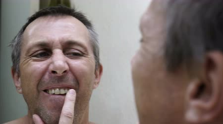зубы : Close up over the shoulder handheld shot of a middle age man looking into a bathroom mirror at his stained teeth and previous dental work.