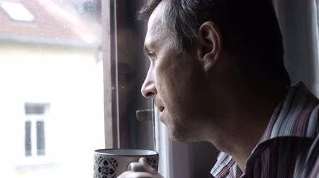 Handheld shot of a man looking out of a window on a cold morning and drinking a cup of coffee.