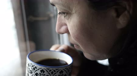 Handheld shot of a woman looking out of a window on a cold morning and drinking a cup of coffee.