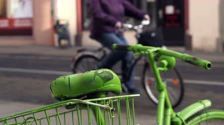 Handheld shot of a person riding past a stationary green bicycle in an urban as a concept for a green and healthy city with people using ecologically responsible transportation.
