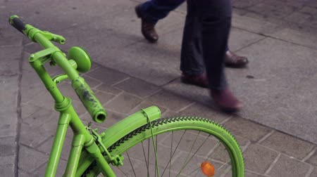 A green colored bike parked on the sidewalk with people walking past signifying a green and healthy city and lifestyle.