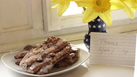 Dolly shot of a note with the message Thanks Mom with a bouquet of flowers and some baked pastries on a plate by a window.
