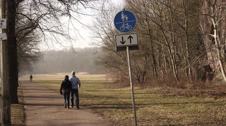 A male and female couple doing the healthy lifestyle activity of walking in a park on a footpath on a cold day away from the camera.