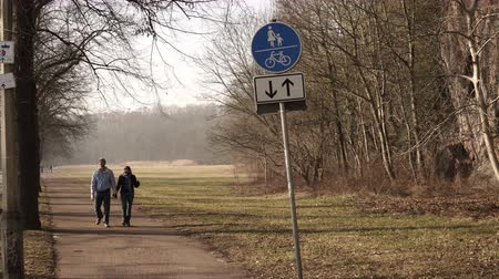 A male and female couple doing the healthy lifestyle activity of walking in a park on a footpath on a cold day towards the camera.