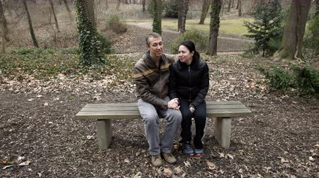 A male and female middle age couple spending quality time together and talking on a park bench enjoying their romantic time with each other during a day in early spring.