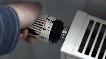ajustando : Close up shot of an anonymous person turning up the heat and then turning down the heating control knob on a radiant hot water heater.