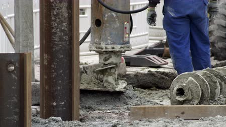 broca : Handheld medium long shot of an industrial post-hole auger drilling head making a hole for pilings on a construction site.