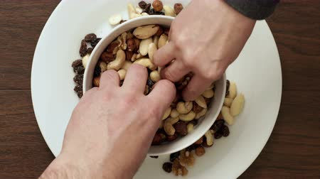 avelã : A closeup shot of a couple eating a bowl of mixed nut and raisins trail mix which is a healthy vegetarian snack. Stock Footage