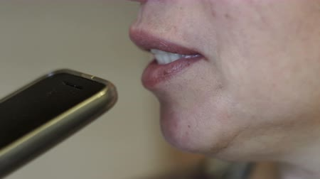 сплетни : Extreme close up handheld shot from the side of a middle age woman leaving a voicemail message with her cellular phone.