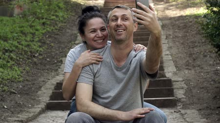 сплетни : Man outside sitting on some steps in a video call on his cellular phone and an affectionate woman approaches him and leans over his shoulder.