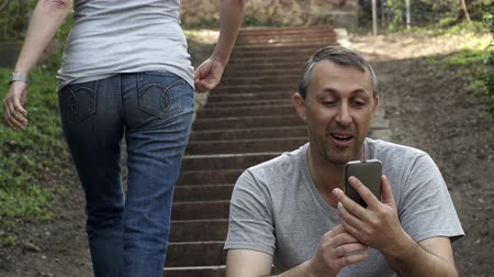 pletyka : Middle age man sitting on outdoor steps talking in a video call on his mobile phone while an anonymous person walks up the stairs past him. Stock mozgókép