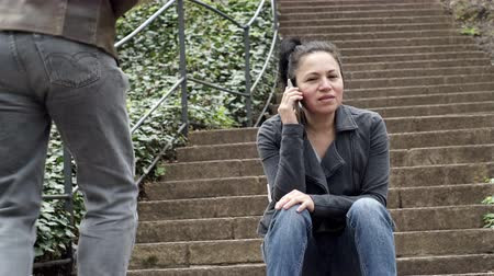 мобильный телефон : Medium shot of a middle age woman sitting on outdoor steps while in a conversation on her mobile phone and an anonymous male person walks up the steps beside her. Стоковые видеозаписи