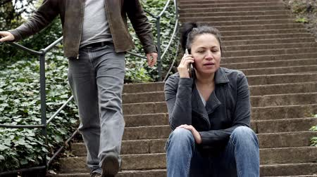 pletyka : Outdoor shot of a middle aged woman in a mobile phone call while sitting on outdoor stairs and a man walks down the stairs past her.