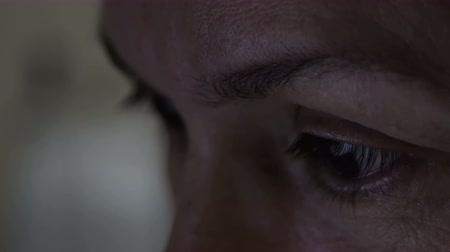 hodinky : Dark evening or night shot of the closeup on the eyes of a middle age woman who is looking at some type of screen. Dostupné videozáznamy