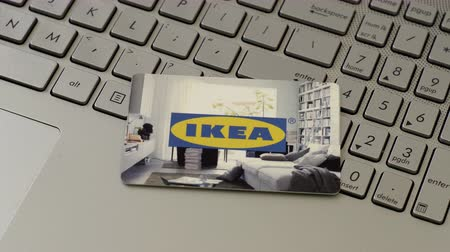 prepaid : HALLE, GERMANY - APRIL 30, 2017: An anonymous person puts an IKEA gift card used for online shopping onto the keyboard of a laptop. Stock Footage