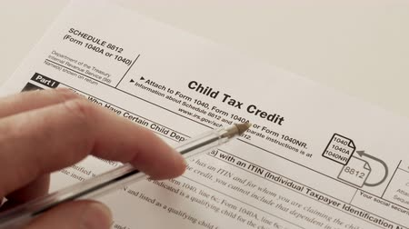 imposto : An anonymous person reading the IRS form 1040 schedule 8812 used to obtain a child tax credit as a way of promoting family development or population growth and working families.