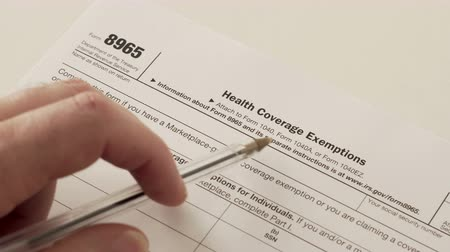 An anonymous person reading the IRS form 8965 used to obtain a health care coverage exemptions that reduce the amount of income tax paid by the claimant.