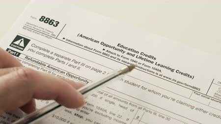 An anonymous person reading the Internal Revenue Service form 8863 which is used for income tax reduction or credits for education fees that have been paid by the claimant. Stock Footage