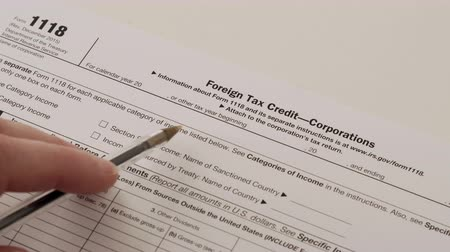 Close up of an anonymous accounting person reading an Internal Revenue Service form 1118 used for claiming corporate foreign tax credits while filing income tax. Stock Footage