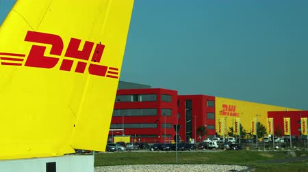 SCHKEUDITZ, GERMANY - SEPT 29, 2017: Static shot of the DHL Courier building and the front sign that marks the location of the package sorting facility industrial complex facility..