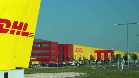 SCHKEUDITZ, GERMANY - SEPT 29, 2017: Pan to a wide shot of the DHL Courier building from the front sign that marks the location of the package sorting facility industrial complex.. Stock Footage
