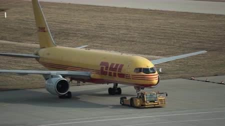 SCHKEUDITZ, GERMANY - APRIL 10, 2018: Handheld closeup shot of a DHL Courier cargo jet being taxied on the runway at the airport near their package sorting facility.