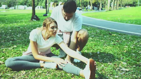 young couple in love exercise on the grass field.