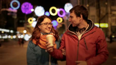 друзья : Young happy couple: man and attractive girl walking down the street city at evening night