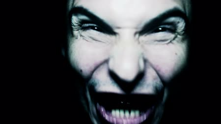 кричать : Horror scene with screaming scary human face with a harsh light on a black background - Halloween concept with young man with open mouth and teeth Стоковые видеозаписи
