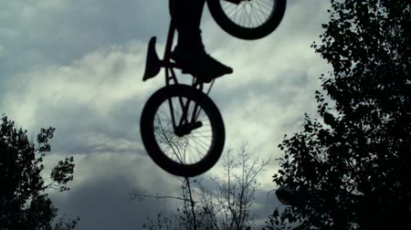 talaj : Silhouette of a young man performing BMX mountain bike sport jump. Extreme speed Stock mozgókép