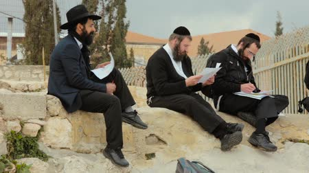 tallit : JERUSALEM, ISRAEL - FEBRUARY 10, 2015: A group of American Orthodox Jewish read the prayer in the ruins on roof of Old city of Jerusalem Stock Footage