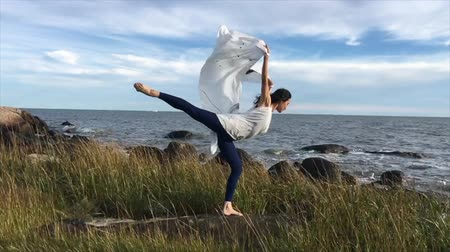 колготки : Woman with billowing white fabric, dancing in the wind at Hammonasset Beach in Madison, Connecticut. Стоковые видеозаписи