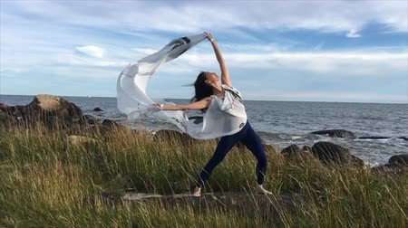 especifico : Mujer con tela blanca ondulante, bailando en el viento en Hammonasset Beach en Madison, Connecticut. Archivo de Video