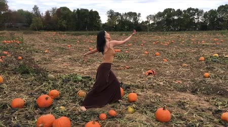 especifico : Adult woman dancer dressed in earth tones, dancing in a farm field with pumpkins at autumn harvest time in Ellington, Connecticut.