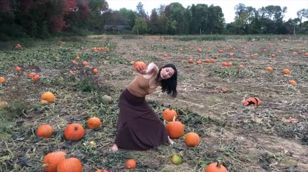 плодородный : Adult woman dancer dressed in earth tones, dancing in a farm field with pumpkins in Ellington, Connecticut. Стоковые видеозаписи