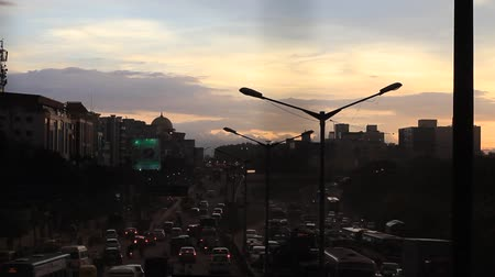Slow moving traffic in Bangalore city, sun sets in the background.