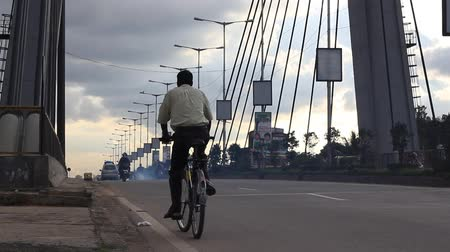 bangalore : Man bicycling though a hanging bridge on a cloudy evening, Lock down shot