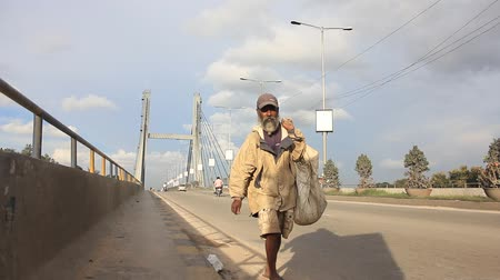 bangalore : A Rag-picker walking on bridge and plastic bag lying on road