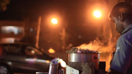 bangalore : Man selling steamed peanuts in street at night Stock Footage