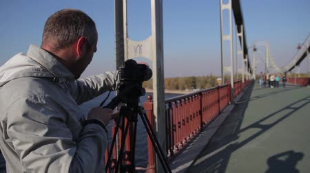 canon : Man (male) cameraman (photographer) with a camera DSLR on a tripod in the city shoots video (taking photo pictures). Kyiv. Ukraine Stock Footage