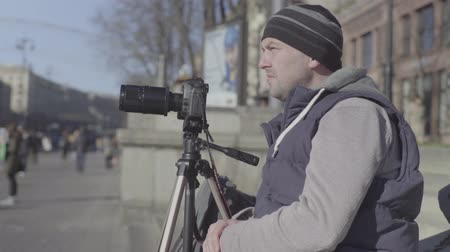 verslaggever : Man (male) cameraman (photographer) with a camera DSLR on a tripod in the city shoots video (taking photo pictures). Kyiv. Ukraine Stockvideo